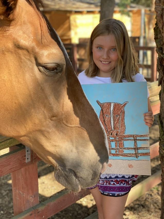 Dziewczynka na obozie konnym z rysunkiem konia